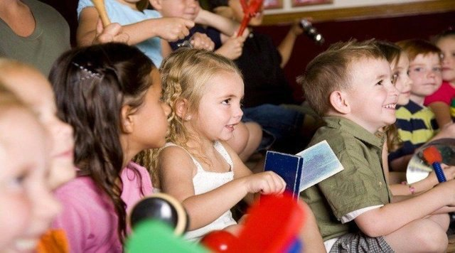 an audience of children learning magic tricks during workshop magic shows